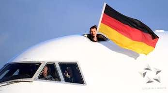 Nach der Landung des Flugzeugs mit dem deutschen Olympiateam an Bord wird eine Deutschlandfahne aus dem Cockpit gehalten. FotoArne Dedert