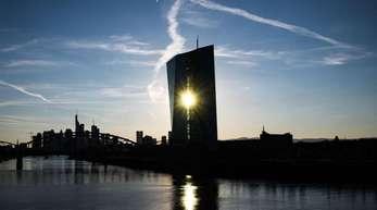 Die untergehende Sonne scheint zwischen den zwei Gebäudeteilen der EZB-Zentrale hindurch.