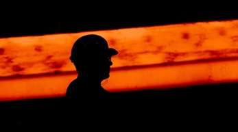 Die Silhouette eines Stahlarbeiters vor glühendem Stahl.