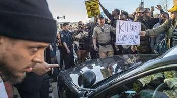 Demonstranten umringen ein Polizeiauto bei einem Protest gegen die Erschießung eines unbewaffneten Mannes durch zwei Polizisten.