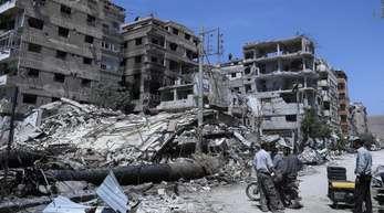 Menschen stehen vor zerstörten Gebäuden in Duma. Hier soll ein mutmaßlicher Chemiewaffenanschlag passiert sein.