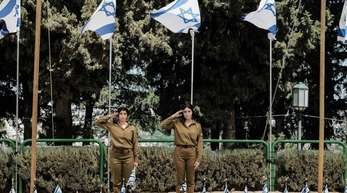 Israelische Soldatinnen salutieren in Jerusalem vor Soldatengräbern.