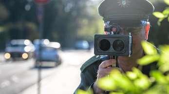 An einer Grundschule in München misst ein Polizist mit einer Laserpistole die Geschwindigkeit vorbeifahrender Fahrzeuge.