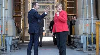 Bundeskanzlerin Angela Merkel begrüßt den französischen Präsidenten Emmanuel Macron im Humboldt-Forum im Berliner Schloss.
