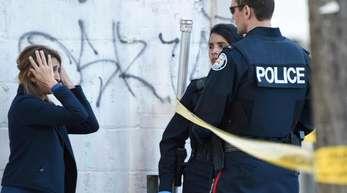Polizisten sprechen mit einer Frau nachdem ein Mann mit einem Lieferwagen zehn Menschen getötet hatte.