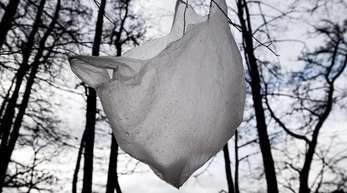 Eine weggeworfene Plastiktüte flattert im Wind an einem Baum im Wald.