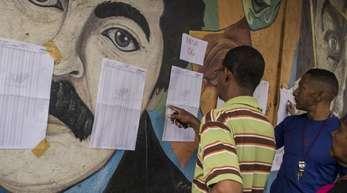 Menschen in Caracas überprüfen Wahllisten, im Hintergrund ein Wandgemälde mit dem Porträt Maduros.