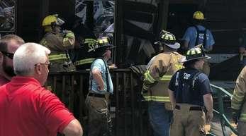 Einsatzkräfte der Feuerwehr stehen vor einem Restaurant, in das ein Mann sein Auto gelenkt hat.