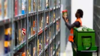 Ein Mitarbeiter von Amazon Fresh packt im Depot der Firma die bestellten Waren in eine Transporttasche.