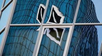 In einer Spiegelfassade verzerrt: Das Logo der Deutschen Bank.