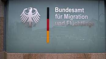 """Der Schriftzug """"Bundesamt für Migration und Flüchtlinge"""" an der Scheibe einer BAMF-Außenstelle."""