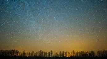 Der Sternenhimmel über einem Feld im Oderbruch in Brandenburg.