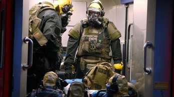 SEK-Beamten mit Atemschutzmasken und Schutzanzügen stehen in einem Fahrzeug vor einem Wohnkomplex. Der in Köln verhaftete Tunesier soll seine Vorbereitungen für einen Terroranschlag mit hochgiftigem Rizin bereits weitgehend abgeschlossen haben, als die