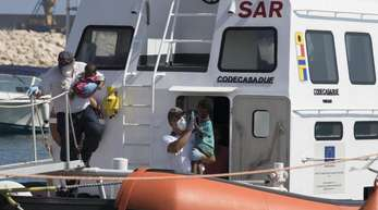 Sanitäter tragen Kinder von Bord eines Schiffes der italienischen Küstenwache.