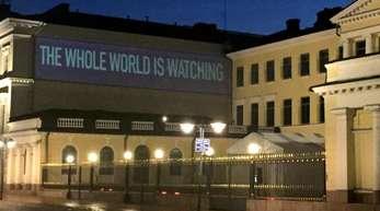 Der Schriftzug «The Whole World is Watching» wird an eine Wand am Präsidentenpalast in Helsinki projiziert.