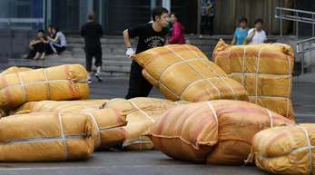 Ein Arbeiter in Peking:Die wirtschaftliche Entwicklung liegt auch weiter über der Vorgabe der Regierung in Peking, die für das ganze Jahr eigentlich nur rund 6,5 Prozent anstrebt.