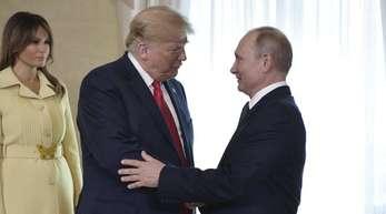 Donald Trump und Wladimir Putin (r) geben sich die Hand vor ihrem bilateralen Treffen.