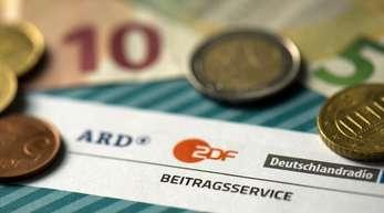 Münzgeld liegt auf Formularen für den Rundfunkbeitrag von ARD, ZDF und Deutschlandradio.