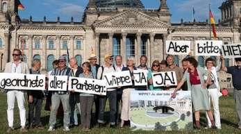 Anhänger des Vereins Berliner Historische Mitte demonstrieren auf der Wiese vor dem Reichstagsgebäude.