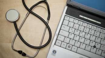 Ein Stethoskop liegt neben einem Laptop.