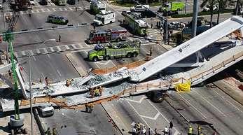 Rettungskräfte arbeiten an einer eingestürzten Brücke auf dem Gelände einer Universität nahe der US-Metropole Miami.