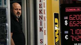 Ein Ladenbesitzer steht neben einer Anzeigetafel, die die Wechselkurse der türkischen Lira anzeigt.