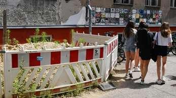 Absperrungen an einer maroden Häuserwand sind auf dem Gelände einer Berliner Schule zu sehen.