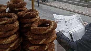 Ein türkischer Simit-Verkäufer vertreibt sich die Wartezeit auf Kunden mit der Zeitungslektüre.