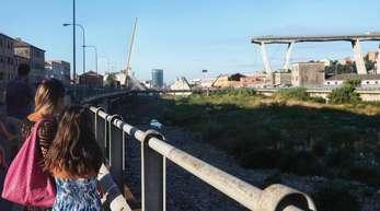 Der Tag danach: Passanten blicken auf die eingestürzte Autobahnbrücke.