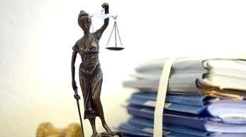 Die modellhafte Nachbildung der Justitia steht auf dem Tisch eines Richters.