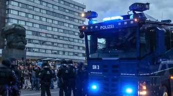 Polizisten sichern mit einem Wasserwerfer eine Demonstration vor dem Karl-Marx-Denkmal.