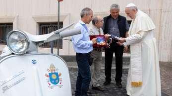Papst Franziskus (r) bekam von Vertretern eines Vespa-Clubs aus Italien eine Vespa geschnekt.