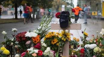 Ein Holzkreuz und zahlreiche Blumen und Kerzen stehen in Chemnitz am Tatort.