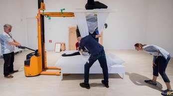 Behutsam wird die schwarze Riesenmaus aus dem Werk «Mann und Maus» der Künstlerin Katharina Fritsch auf ein Bett heruntergelassen.