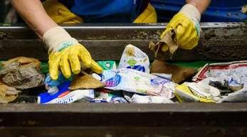 Eine Mitarbeiterin arbeitet an einem Fließband in der Sortieranlage für Verpackungsabfälle.
