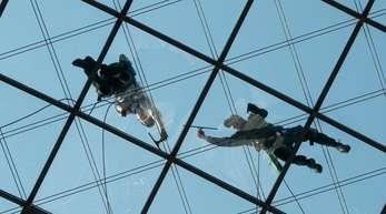 Gebäudereiniger putzen in 27 Meter Höhe das gläserne Dach des World Trade Centers in Dresden.