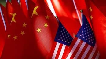 Nationalflaggen von den USA und China stecken an einer Fahrrad-Rikscha.