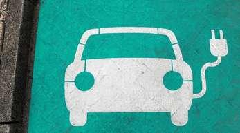 Ein stilisiertes Auto auf grünem Grund markiert einen Parkplatz mit Ladesäule für Elektrofahrzeuge.