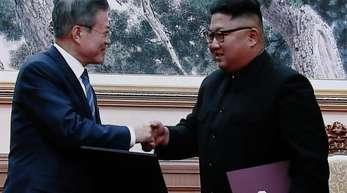 Moon Jae In und Kim Jong Un geben sich nach der Unterzeichnung der Dokumente die Hand.