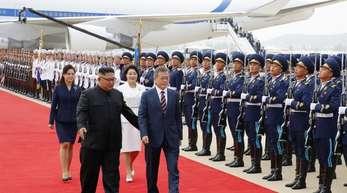 Moon Jae In und seine Ehefrau Kim Jung Sook schreiten in Begleitung von Kim Jong Un und dessen Ehefrau Ri Sol Ju nach ihrer Ankunft auf dem Internationalen Sunan Flughafen die Ehrengarde ab.