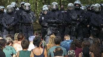 Umweltaktivisten sitzen im Hambacher Forst vor einer Polizeikette.