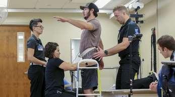 Jered Chinnock (3.v.l) seht mit seinem Therapieteam in der Mayo Clinic. Mittels elektrischer Rückenmarkstimulation und 43 Wochen Rehabilitationstherapie konnte der Patient mit 331 Schritten 102 Meter zurücklegen.