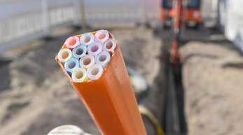 Farbige Leerrohre, in die später die Glasfaserkabel verlegt werden, ragen aus einem Graben auf einer Baustelle im brandeburgischen Grassau.