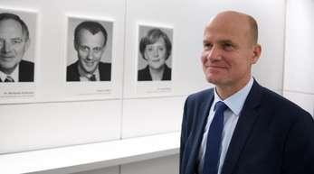 Illustre Vorgänger: Unions-Fraktionschef Ralph Brinkhaus steht vor einer Fotogalerie ehemaliger Fraktionschefvorsitzender.