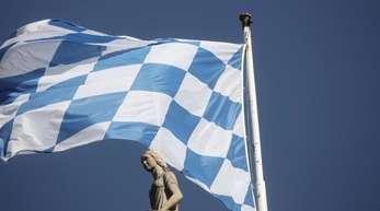 Eine weißblaue Fahne weht auf dem Maximilianeum, dem Sitz des Bayerischen Landtags.