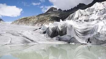 Arbeiter befestigen weiße Spezialdecken am Rhonegletscher, um den ältesten Gletscher der Alpen vor dem Schmelzen zu bewahren.