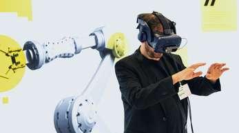 """Ein Besucher mit VR-Brille in der Fraunhofer-Erlebniswelt """"#Zukunftsarbeit"""" in Berlin."""