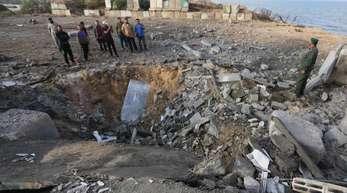 Palästinensische Männer inspizieren am Ort des israelischen Luftangriffs die Schäden.
