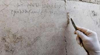 Ein Archäologe zeigt an einer Mauer in Pompeji die Kohle-Inschrift, die auf die Eruption des Vesuv im Jahr 79 verweist.
