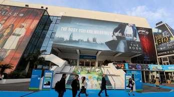 Besucher spazieren vor dem Festival-Palais der TV-Messe MIPCOM in Cannes.
